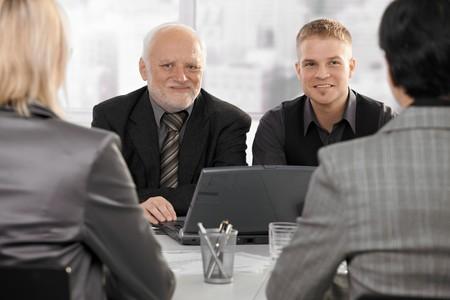 verlobung: Senior und junior Gesch�ftsleute sitzen bei Treffen mit Gesch�ftsfrauen l�chelnd.