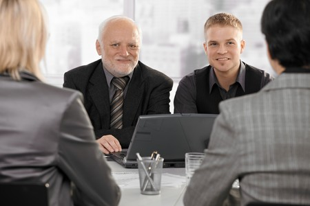 employee satisfaction: Smiling senior and junior businessmen sitting at meeting with businesswomen. Stock Photo