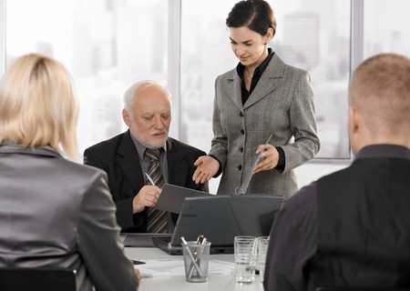 businessmeeting: Secretary getting contract to sign by senior executive at businessmeeting. Stock Photo