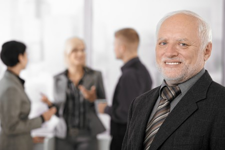 Portrait of senior businessman smiling at camera, team discussing work in background. Stock Photo - 7791884