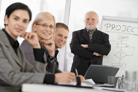 Confident businesspeople smiling at camera at training, senior executive standing at background with arms folded. photo
