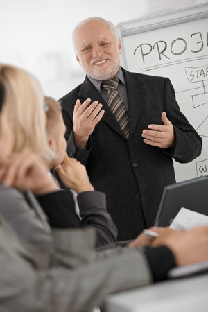 experienced: Experienced senior executive explaining work to colleagues, gesturing, smiling, standing at whiteboard.