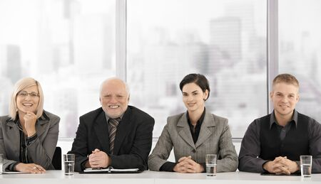 workplace: Formal businessteam portrait of different generations sitting at meeting table, smiling at camera.