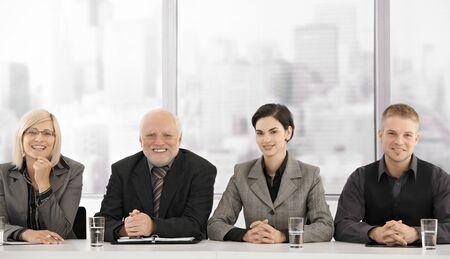 Formele businessteam portret van verschillende generaties zit op vergader tafel, glimlachend in de camera. Stockfoto