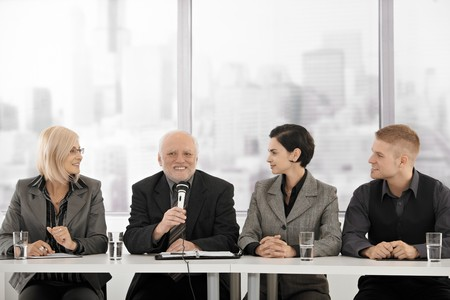 Businessteam on meeting, senior executive talking into microphone giving speech, smiling. Stock Photo - 7791872