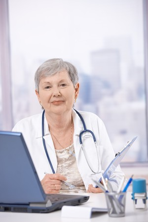 Senior female doctor, working at desk, making notes. photo