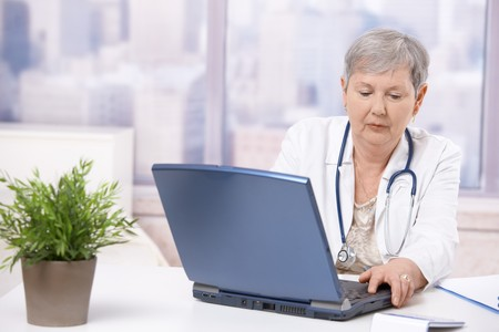 Senior female doctor, working at desk, using laptop computer. Focusing at screen. photo