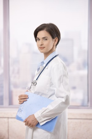 Portrait of attractive female doctor walking on hospital corridor, smiling at camera. Stock Photo - 7792035