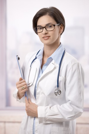 Portrait of attractive female doctor holding clipboard indoor, smiling. Stock Photo - 7792076