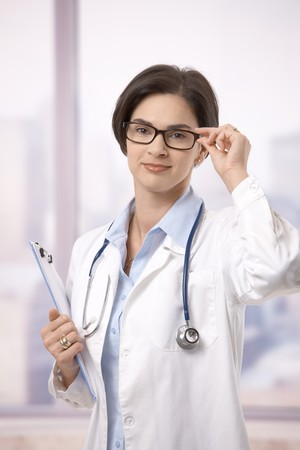Portrait of attractive female doctor holding clipboard and glasses indoor, smiling at camera. photo