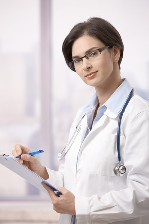 Attractive female doctor standing on hospital corridor doing paperwork, looking up at camera. photo