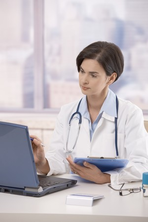 Attractive mid-adult female doctor sitting at desk in office working on laptop computer. Stock Photo - 7792048