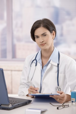 Attractive mid-adult female doctor sitting at desk in office doing paperwork, looking up and smiling at camera. photo