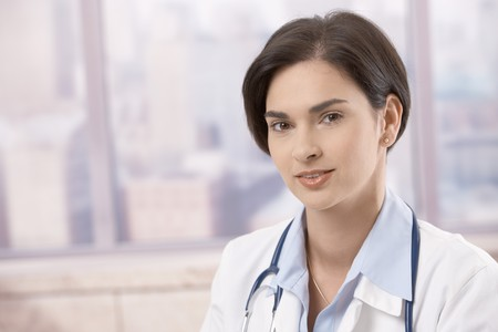 Closeup portrait of attractive young female doctor looking at camera, smiling. Copyspace on left. photo
