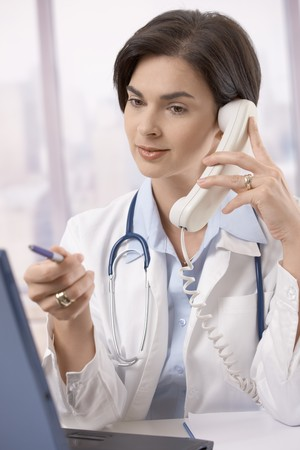 Mid-adult female physician working at desk, talking on phone and looking at computer screen. photo