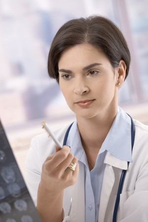 Female doctor working on diagnosis, examining x-ray in office. Stock Photo - 7792073