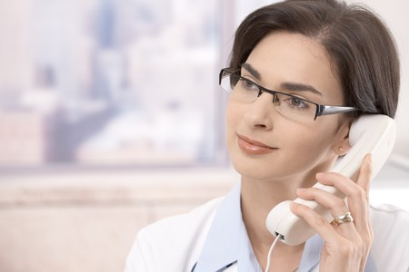 Attractive mid-adult caucasian female doctor talking on landline phone, looking away. Stock Photo - 7792074