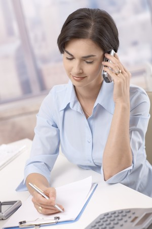 Portrait of smiling businesswoman using cellphone, taking notes at office desk. photo