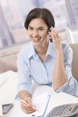 Laughing businesswoman on mobile phone call, sitting in office at desk, taking notes. photo