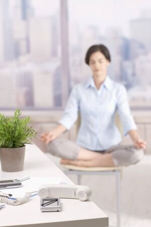 Not answering phone in skyscraper office, female office worker doing yoga meditation in background. Stock Photo - 7792008