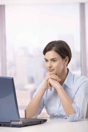 Businesswoman looking at computer screen sitting in office, concentrating.