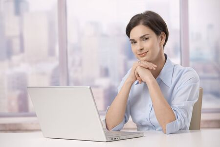 Portrait of female professional sitting at skyscraper office table with laptop computer, smiling at camera. photo