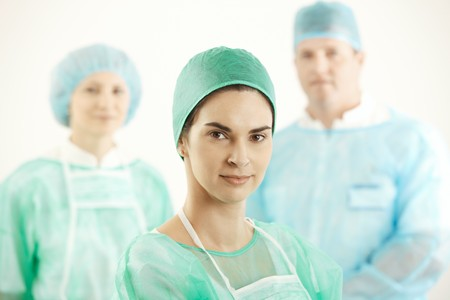 Confident surgeon with colleagues in background, wearing hospital scrubs. photo