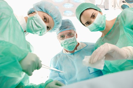 Portrait of surgeons at work, operating in uniform, looking at camera. photo