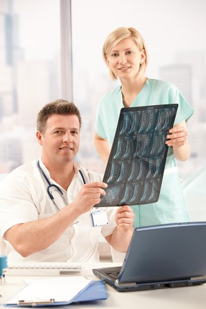 Portrait of smiling doctor and nurse holding x-ray image in office. Stock Photo - 7792118