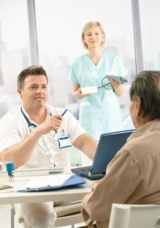 blood pressure gauge: Smiling doctor discussing diagnosis with patient, smiling nurse holding blood pressure gauge.