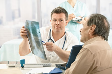 a diagnosis: Doctor showing diagnosis of x-ray image to older patient sitting at office desk. Stock Photo