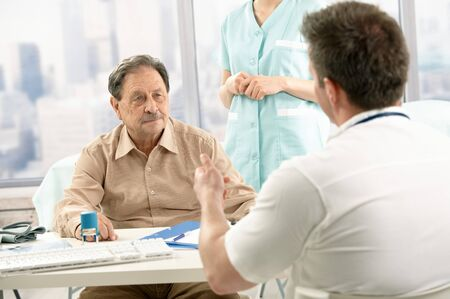 Medical doctor discussing diagnosis with elderly patient at office, nurse in background. Stock Photo - 7792119