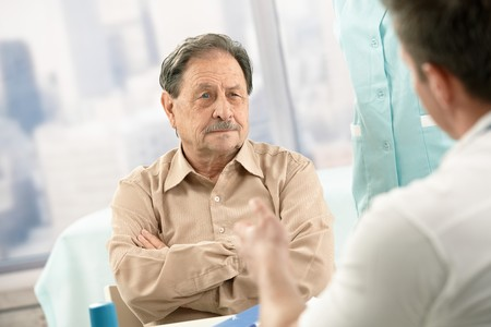 image consultant: Senior patient listening to doctors explanation on consultation.
