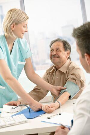 clinician: Smiling nurse measuring blood pressure of elderly patient, smiling at doctors desk.
