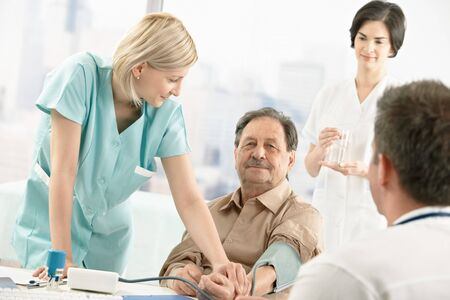 Nurse assisting doctor with measuring patient blood pressure in office. Stock Photo - 7792122