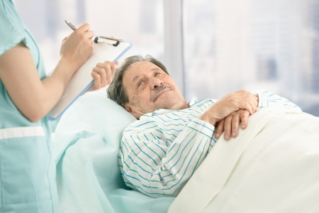 sick day: Nurse holding clipboard, taking notes of old patient lying in hospital bed. Stock Photo