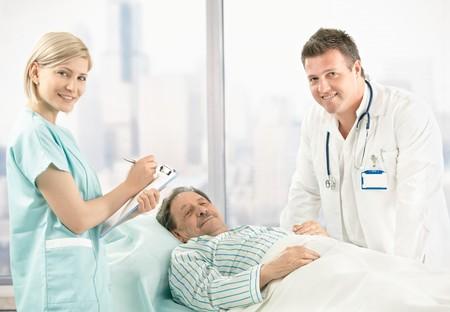 enfermera con paciente: Retrato de m�dico, la enfermera y el paciente, antiguo paciente en la cama de hospital, m�dico y enfermera en visita.  Foto de archivo