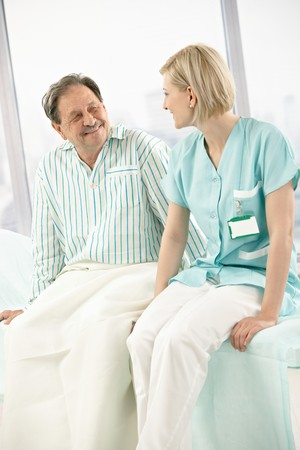 Nurse and patient sitting on hospital bed together, chatting, smiling. photo