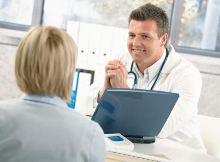 medico con paciente: Doctor sonriente hablando al paciente en el escritorio de la Oficina.  Foto de archivo