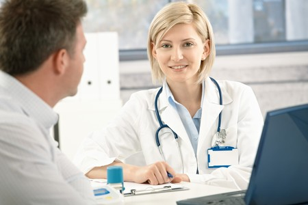 Smiling doctor talking to patient in office. Stock Photo - 7792112