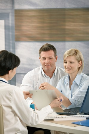 Couple discussing results with physician in doctor's office, smiling. Stock Photo - 7792116