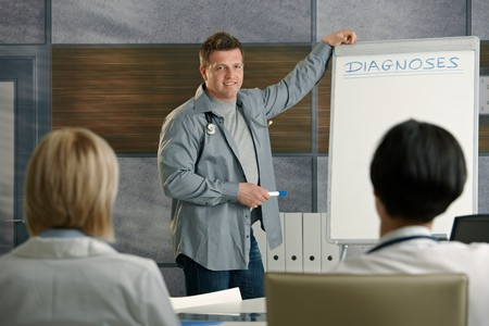 clinician: Medical doctors listening to presentation of mid-adult expert on diagnoses.