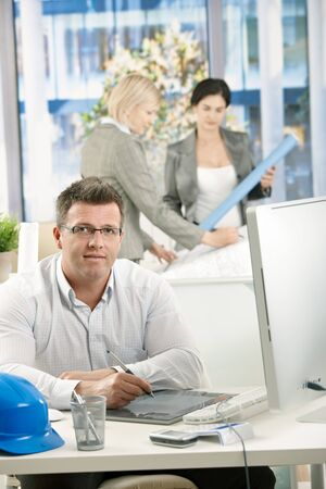 Architect sitting in office, designers working together in background. photo