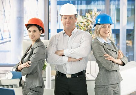 Architect team wearing hardhat in office, posing for portrait, looking at camera, smiling. photo