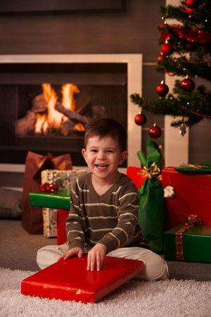 Happy little boy sitting on floor wrapping out christmas present in front of christmas tree and fireplace. Stock Photo - 7792175