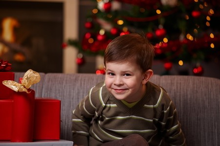 Portrait of happy little boy at christmas eve, looking at camera, smiling.