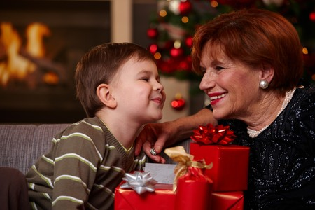 getting together: Portrait of happy grandmother and grandson looking to each other over christmas presents, smiling.