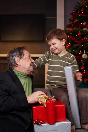 Small boy getting christmas present from happy grandfather, looking each other, smiling.   photo