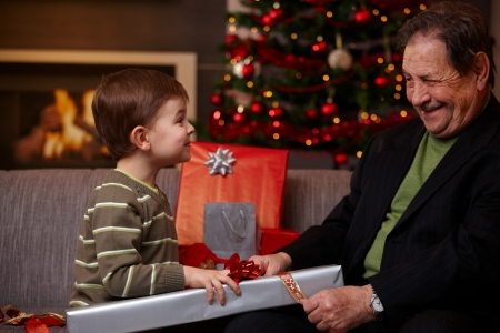 Small boy helping grandfather wrapping christmas gifts, smiling happily.