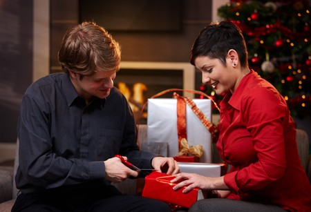 Young couple sitting on couch at home, wrapping christmas presents together, smiling.   photo